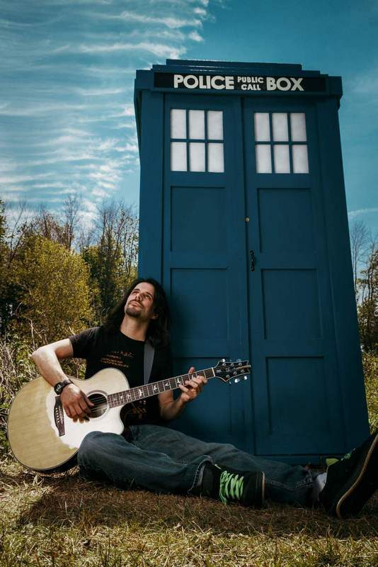 Scott Paris and his guitar outside of a tardis