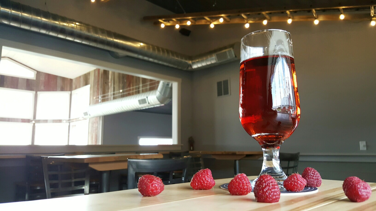 A glass of Brambleberry cider and some red raspberries