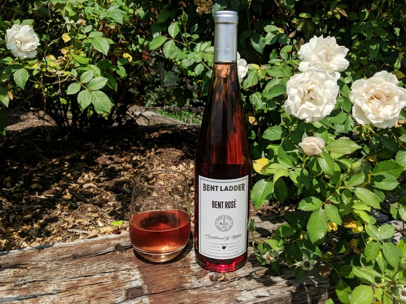 A bottle and glass of Bent Rosé surrounded by flowers