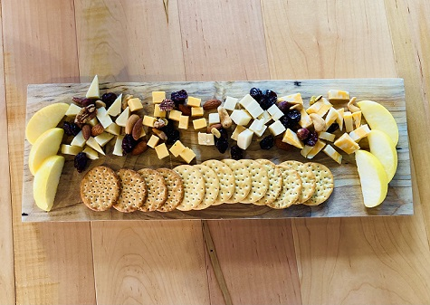 Various selection of cheeses, fruit, and crackers make up our cheese board
